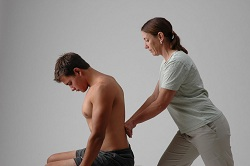 Picture of client sitting on table receiving treatment on his back
